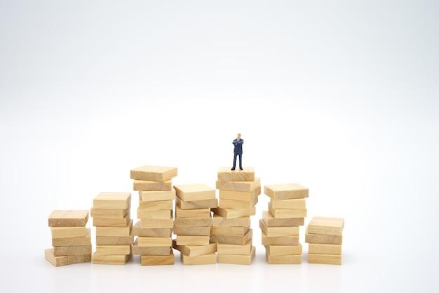 Miniatuur zakenman die zich op stapel documenten bevindt