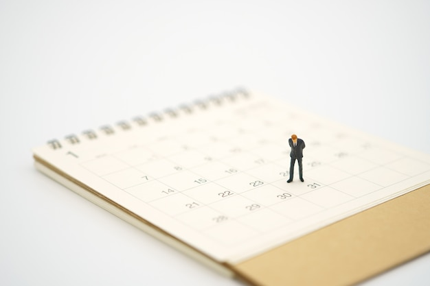 Miniatuur zakenman die zich op witte kalender bevindt