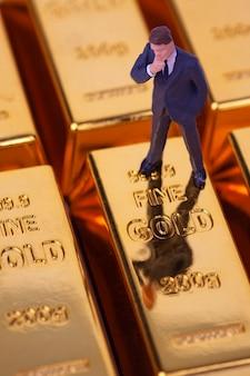Miniatuur zakenman staande op goudstaaf
