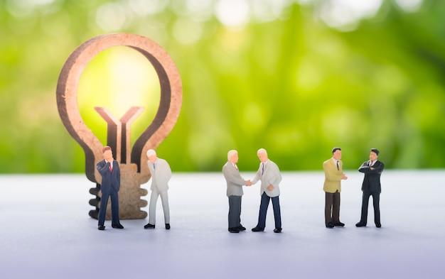 Miniatuur zakenmanhandenschudden met ideeconcept die als achtergrondvennootschap gebruiken concep