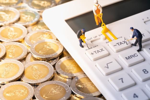 Miniatuurarbeiders die belastingsknoop op calculator op stapel van muntstukken graven
