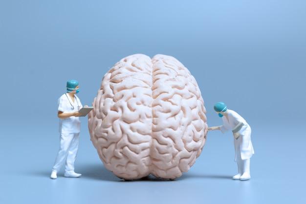 Miniatuurarts die de ziekte van alzheimer en dementie van het concept van de hersenen, de wetenschap en de geneeskunde controleert en analyseert