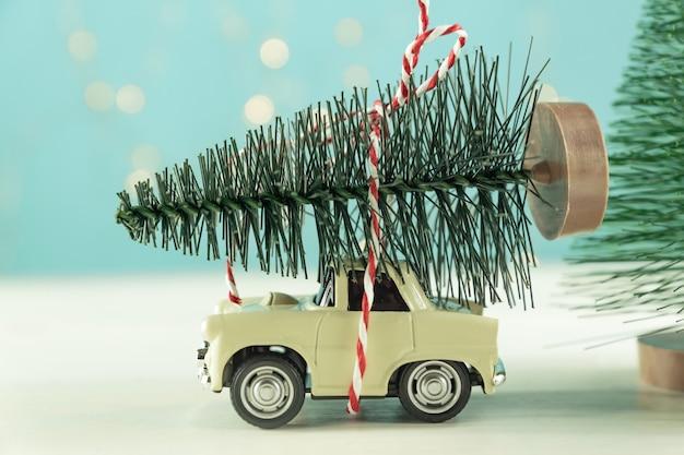 Miniatuurauto met dennenboom op houten