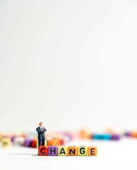 Miniatuurcijferzakenman in donkerblauw kostuum bevindend achtereind van kleurrijk van veranderen alp