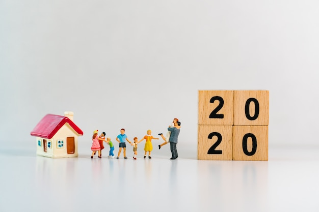 Miniatuurfamilie staande met mini-huis en 2020 houten blokken