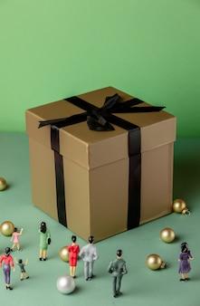 Miniatuurfiguren van mensen en grote geschenkdoos