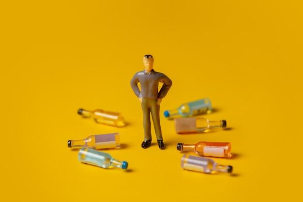 Miniatuurfiguur van een man met alcoholflessen om zich heen