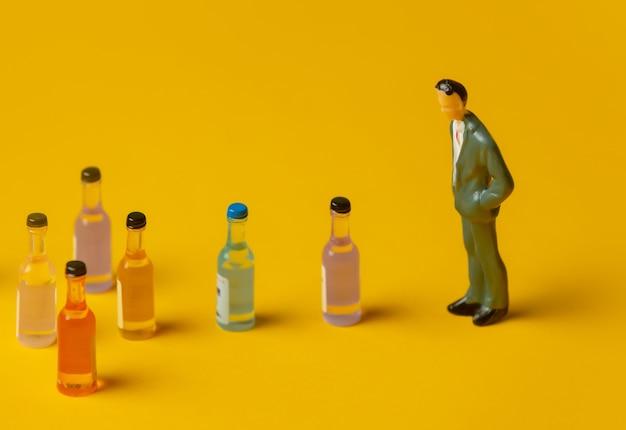 Miniatuurfiguur van een man met alcoholflessen voor zich