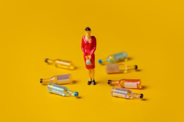 Miniatuurfiguur van een vrouw met alcoholflessen om haar heen