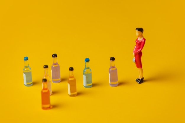 Miniatuurfiguur van een vrouw met alcoholflessen voor haar