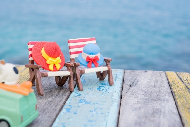 Miniatuurhoeden op ligstoel met overzeese achtergrond.