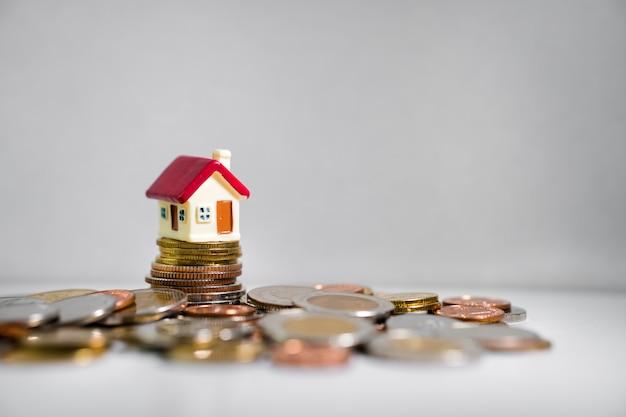 Miniatuurhuis op stapel van muntstukken die als onroerende goederenbezit en financieel concept gebruiken
