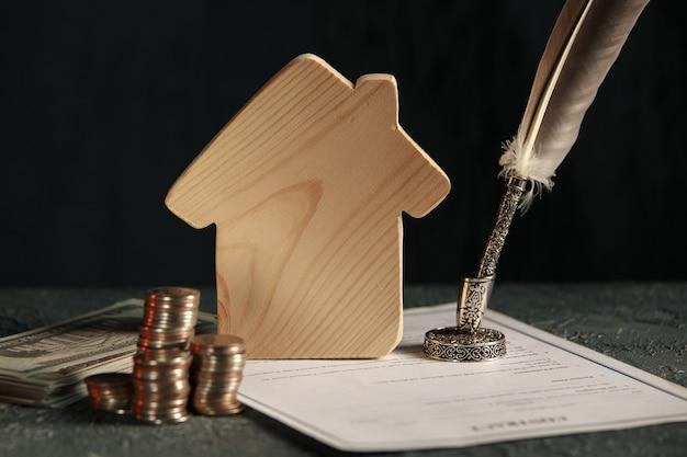 Miniatuurhuisje met geld en belastingpapieren.