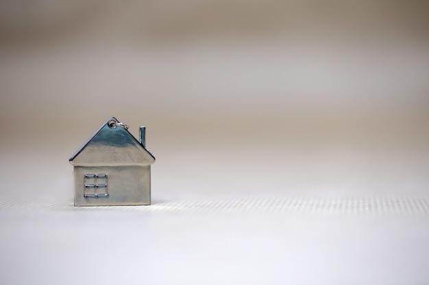 Miniatuurhuisje op onscherpe achtergrond, nieuw huis, onroerend goed, hypothecaire lening, architectonisch concept met kopie ruimte fot tekst