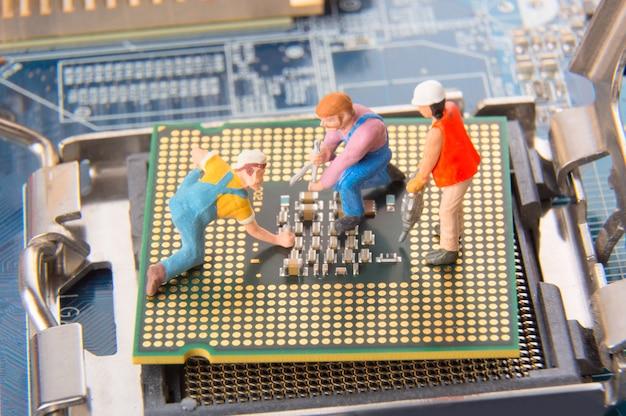 Miniatuuringenieurs of technicusarbeiders die cpu op het moederbord herstellen