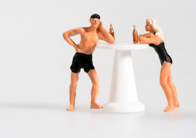Miniatuurman en vrouw die bij een kiosk drinken