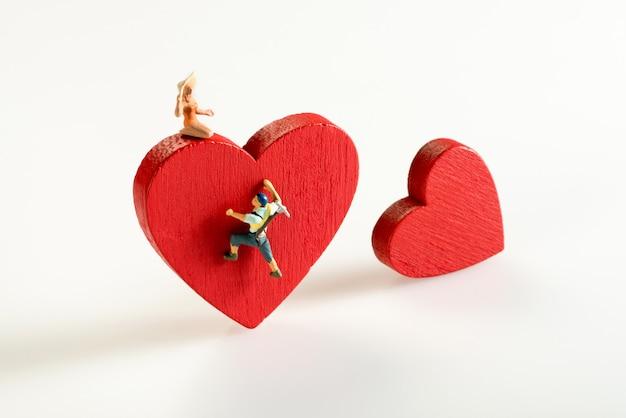 Miniatuurmens die een rood hart beklimt