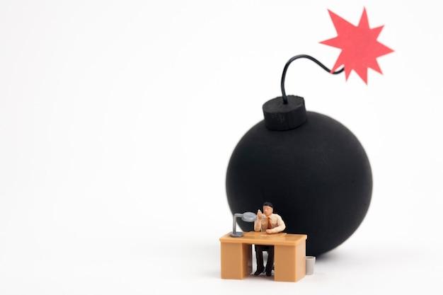 Miniatuurmens die met bom klaar om te exploderen werkt