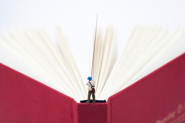 Miniatuurmens die op een boek vist