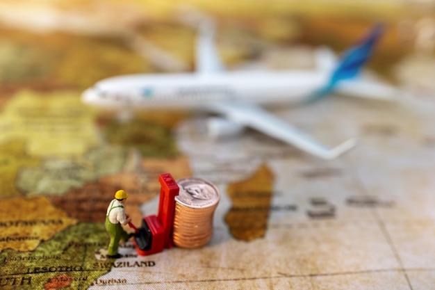 Miniatuurmensen: arbeider die munten in het vliegtuig laadt. verzend- en online bezorgservice concept.