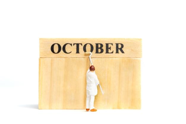 Miniatuurmensen, arbeider die oktober op houten blok op witte achtergrond schilderen.
