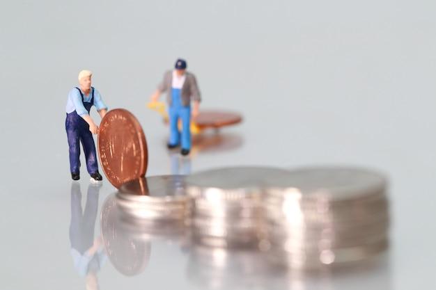 Miniatuurmensen: arbeider met muntstukken, bedrijfsconcept die als achtergrond gebruiken