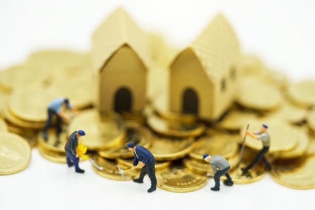 Miniatuurmensen: arbeiders die aan gouden munten met huizen werken.