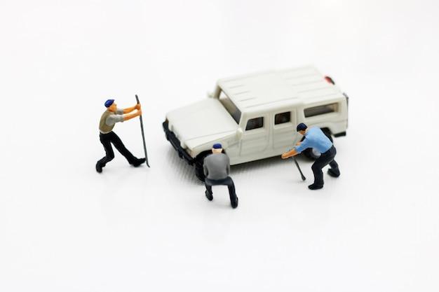 Miniatuurmensen: arbeiders die auto repareren. autoservice, reparatie, onderhoud concept.