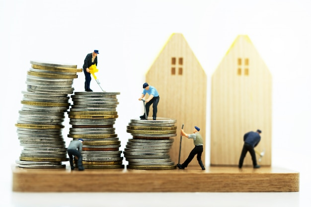 Miniatuurmensen: arbeiders die met hulpmiddelen aan muntstukkenstapel werken met houten huis. renovatie en onroerend goed serviceconcept.