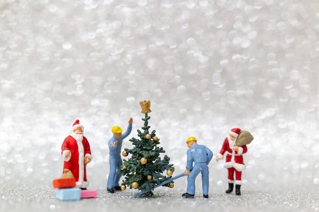 Miniatuurmensen: arbeidersteam bereidt kerstboom voor