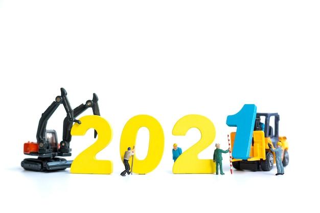 Miniatuurmensen: arbeidersteam bouwt houten nummer 2021, gelukkig nieuwjaarsconcept