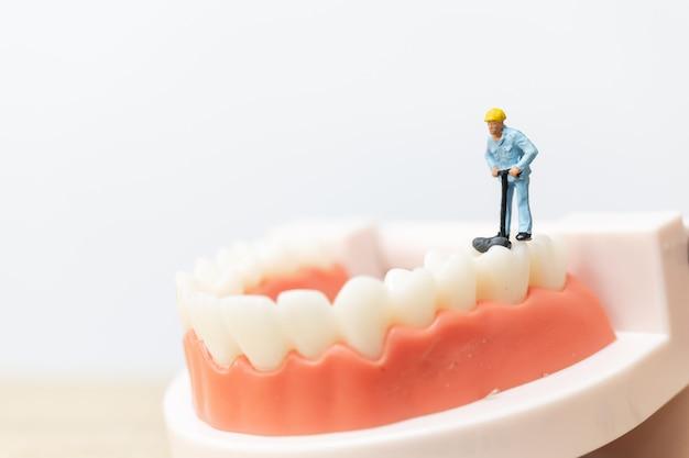 Miniatuurmensen: arbeidersteam dat een tand herstelt
