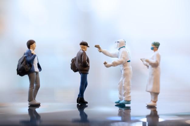 Miniatuurmensen arts die gezichtsmaskers draagt tijdens uitbraak van coronavirus en griep.