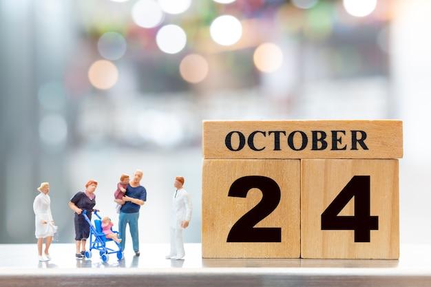 Miniatuurmensen arts en kinderen op houten blok 24 oktober achtergrond. wereld polio dag concept