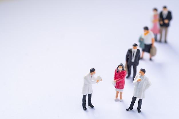 Miniatuurmensen: arts en patiënt op witte achtergrond, gezondheidszorgconcept.