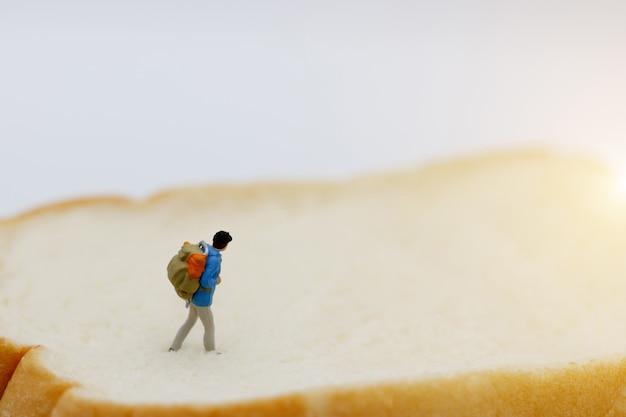 Miniatuurmensen, backpacker die naar bestemming loopt.