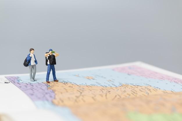 Miniatuurmensen backpacker die op kaart loopt reis- en avontuurconcepten.