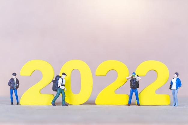 Miniatuurmensen backpacker die zich op houten nummer 2022 bevinden, gelukkig nieuw jaarconcept