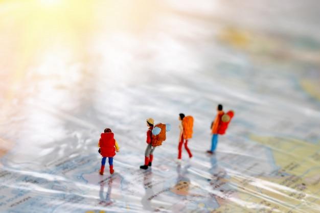 Miniatuurmensen: backpacker die zich op kaart, reisconcept bevinden.