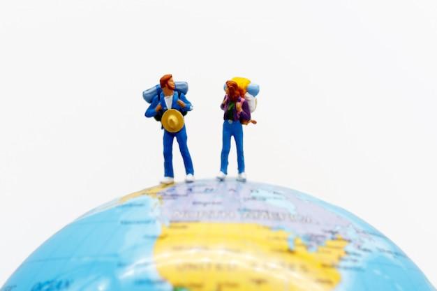 Miniatuurmensen, backpackers ter wereld die naar bestemming lopen.