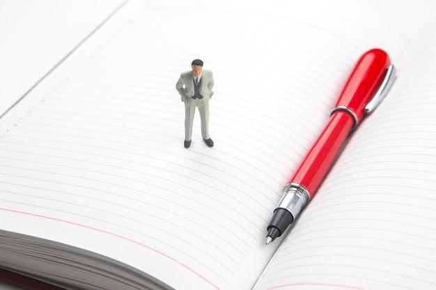 Miniatuurmensen. beeldje van een man op een notitieboekje met een pen. het concept van een ondernemer bij het plannen van hun zaken in het leven