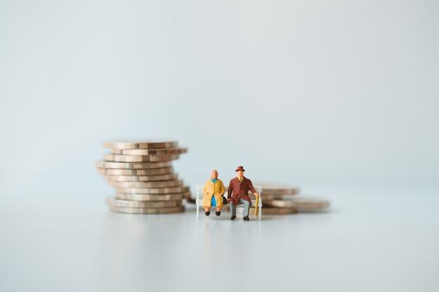 Miniatuurmensen, bejaarde mensen die op stapelmuntstukken zitten die als concept van de baanpensionering gebruiken