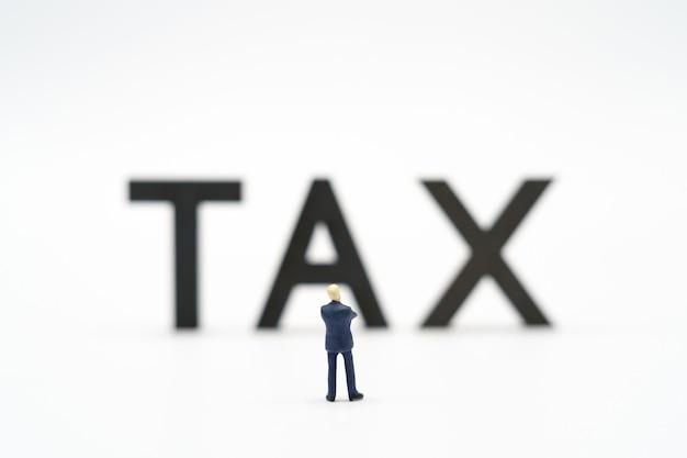 Miniatuurmensen betaal wachtrij jaarinkomen (btw) voor het jaar op rekenmachine.