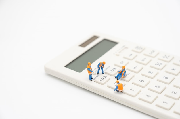 Miniatuurmensen betaalwachtrij jaarinkomen (tax) voor het jaar op rekenmachine.