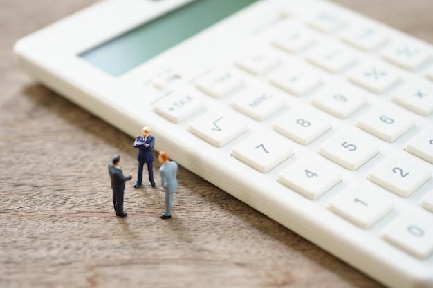 Miniatuurmensen betaalwachtrij jaarlijks inkomen (belasting) voor het jaar op rekenmachine.