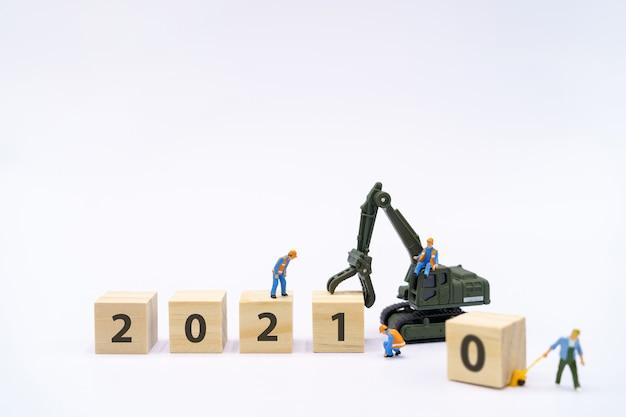 Miniatuurmensen bouwvakker beheer producten met houten blok 2021