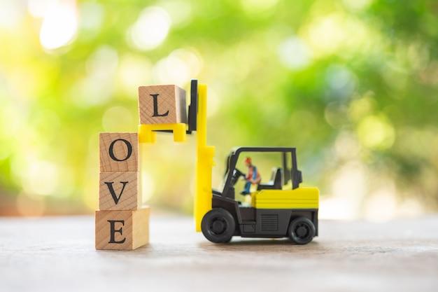 Miniatuurmensen bouwvakker met houten woordliefde