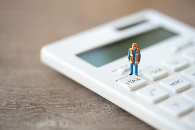 Miniatuurmensen bouwvakker toetsenbord tax-knop voor belastingberekening.