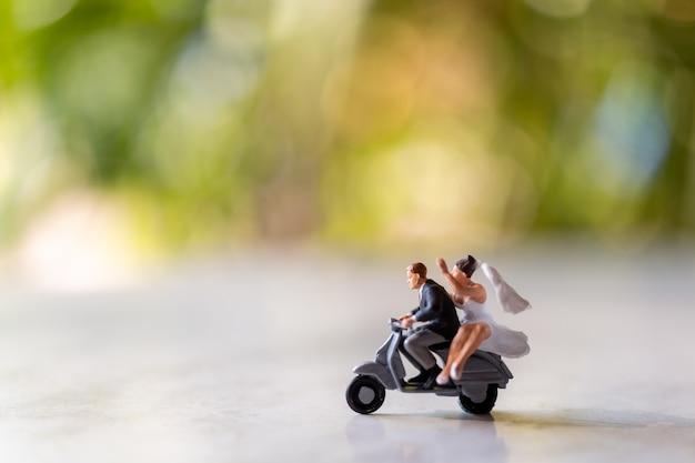 Miniatuurmensen: bruid en bruidegom in openlucht met groene bokehachtergrond en exemplaarruimte voor tekst