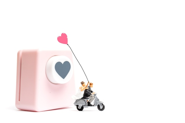 Miniatuurmensen, bruid en bruidegom met hartvormige ponsmachine